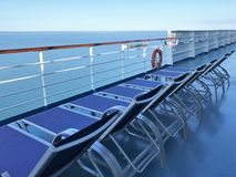 Lounge chairs on a cruise ship deck overlooking the ocean and a beautiful blue sky. Lounge chairs on a cruise ship deck with views of the ocean and a beautiful royalty free stock image