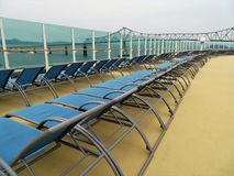 Lounge chairs on a cruise ship deck with views of the Astoria Bridge in Oregon. Empty lounge chairs on a cruise ship deck stock photos