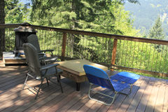 Lounge Chairs on a Deck. Three lounge chairs on a deck, two regular and one full body, outside in front of a view of a forest on a sunny day royalty free stock photo