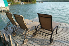 Lounge chairs on a lake front dock Royalty Free Stock Photos