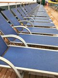 Lounge chairs lined up a cruise ship deck. A row of Lounge chairs lined up a cruise ship deck stock photo