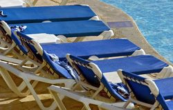 Lounge Chairs Lined up at Pool's Edge Royalty Free Stock Photos