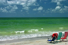 Lounge chairs by ocean Stock Images