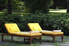 Lounge chairs outside. Two yellow lounge chairs on a patio Royalty Free Stock Photography