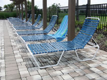 Lounge chairs at pool. Row of blue lounge chairs at a swimming pool Royalty Free Stock Photo