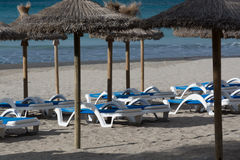 Lounge chairs and straw umbrellas Royalty Free Stock Photography