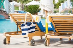 Lounge chairs with striped bag near the pool at the resort royalty free stock photography