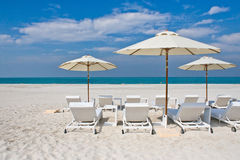 Lounge chairs with sun umbrella on the beach Royalty Free Stock Photos