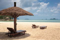 Lounge chairs and sunshade umbrella on the beach Stock Photos