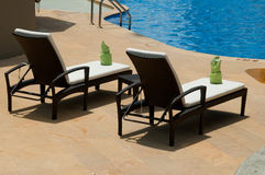 Lounge chairs by the swimming pool Stock Photography
