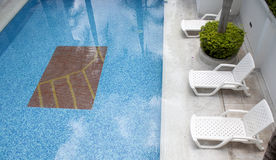 Lounge chairs in a swimming pool Royalty Free Stock Photography