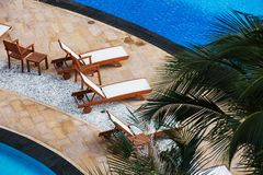 Lounge chairs in a swimming pool invite you Stock Photography