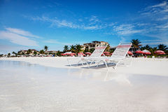 Lounge chairs on tranquil Grace Bay Beach. Beach chaises at water's edge on the soft white sands of Grace Bay Beach, Turks & Caicos royalty free stock photography