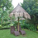 Lounge Chairs and Umbrella made of Haystack Roof. Brown pair of Lounge Chairs and Native Umbrella made of Haystack Roof Stock Photo
