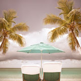 Lounge chairs and umbrella at a tropical paradise beach Royalty Free Stock Photos