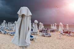 Lounge chairs and umbrellas on empty sand beach vefore the rain with sunlight royalty free stock photography