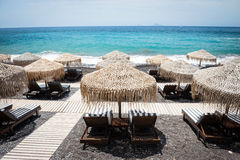 Lounge chairs with umbrellas on the empty White beach, Santorini Stock Photo