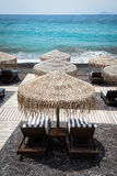Lounge chairs with umbrellas on the empty White beach, Santorini Stock Photos
