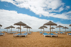 Lounge chairs with umrellas on the empty sandy beach Stock Photo
