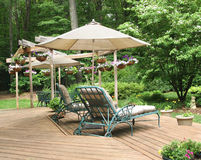 Lounge chairs under patio umbrella. On deck decorated with hanging baskets of petunias Stock Photography