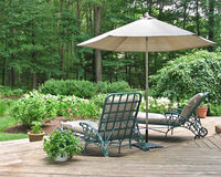 Lounge chairs under patio umbrella. Lounge chairs on wooden deck under patio umbrella Stock Images