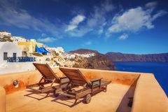 Lounge chairs with a view of the caldera, Oia village, Santorini Stock Photo