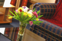 Lounge & flowers. Vase of fresh flowers on a coffee table in a lounge room Stock Photography