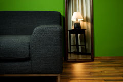 Lounge green room with couch and lamp in mirror Stock Image