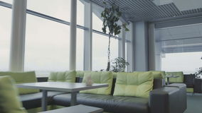 Lounge hall of the airport. The camera moves forward. The action takes place at the airport in the lounge waiting hall. The lounge hall with green sofas, big stock video footage