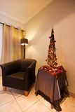 Lounge interior with tub chair and Christmas tree. Lounge interior with tub chair, lamp and decorated traditional African Christmas tree Stock Images