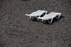 Lounge plastic white beds on black sand beach Stock Photography