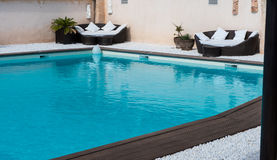Lounge sofas in the pool with Bankirai and white pebble Royalty Free Stock Photo