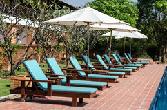 Lounge sunbed beach chairs near swimming pool. In hotel Stock Images