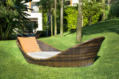 Lounge sunbed in a green garden. Lounge rattan sunbed in a green tropical garden royalty free stock images