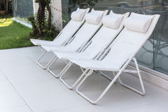 Lounge sunbeds near swimming pool, outdoor near sea Stock Images