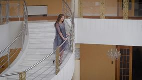 Lounge van de slimme zaal Reusachtige ladders, marmeren vloer, mooie kroonluchters Het meisjesmodel stelt op een ladder De markt stock videobeelden