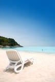 Lounger di Sun sulla spiaggia sabbiosa contro cielo blu Fotografie Stock Libere da Diritti