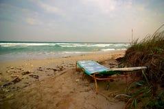 Lounger vazio do sol perto do mar tormentoso no tempo ventoso Fotos de Stock Royalty Free