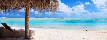 Loungers и зонтик на тропическом пляже Стоковое Изображение RF