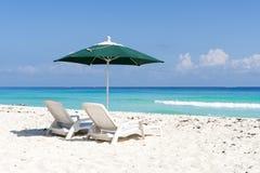 Loungers и зонтик Солнця на тропическом пляже Стоковое Изображение