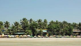 Loungers людей и пляжа под солнечными красочными зонтиками на песке на фоне баров и ресторанов в зеленом p видеоматериал