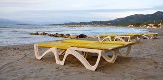 Loungers на пляже морем Стоковые Изображения
