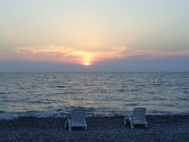 2 loungers на пляже моря на заходе солнца Стоковое Изображение RF