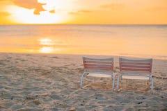 2 loungers на пляже с белым песком на светах захода солнца Стоковое Изображение