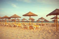Loungers палубы в пляже на заходе солнца. Рай в Алгарве, Португалии Стоковые Изображения RF
