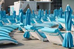 Loungers солнца бирюзы и сложенные зонтики на заднем плане гостиницы, концепции отдыха Стоковые Изображения RF