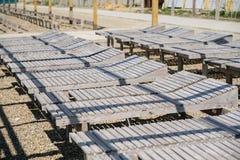 Loungers солнца конца-вверх деревянные на pebbled общественном пляже seashore Взгляд со стороны Стоковое Изображение