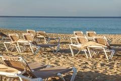 Loungers Солнця и закрытые зонтики на курорте на море, спокойной и расслабленной атмосфере летнего отпуска на заходе солнца Стоковые Изображения