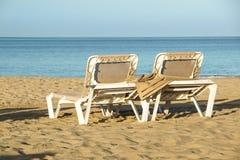 Loungers Солнця и закрытые зонтики на курорте на море, спокойной и расслабленной атмосфере летнего отпуска на заходе солнца Стоковое Изображение RF