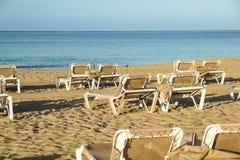 Loungers Солнця и закрытые зонтики на курорте на море, спокойной и расслабленной атмосфере летнего отпуска на заходе солнца Стоковая Фотография